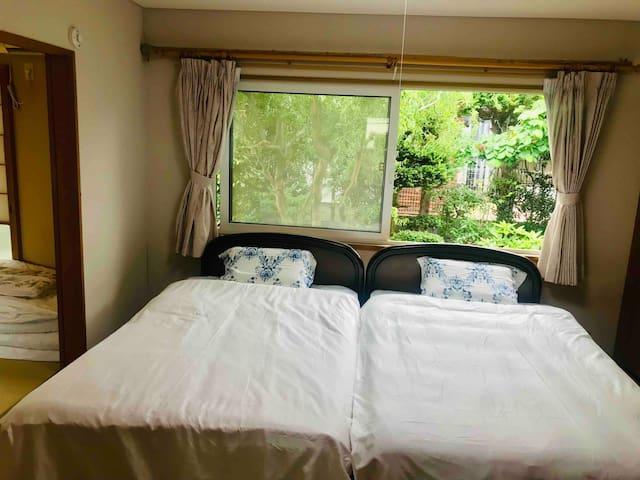 二台のベッドはセミダブルサイズ 庭の向こうには隣のUNIQLOの駐車場がちらりと見えている。 Two beds full-size(W120 cm× L200 cm)
