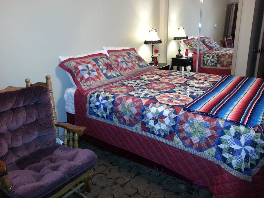 Queen bed with quilt and blanket.