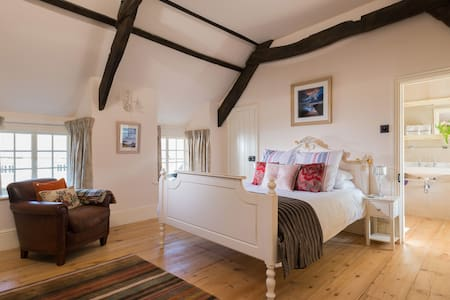 A lovely large room with pine floors and beamed ceiling