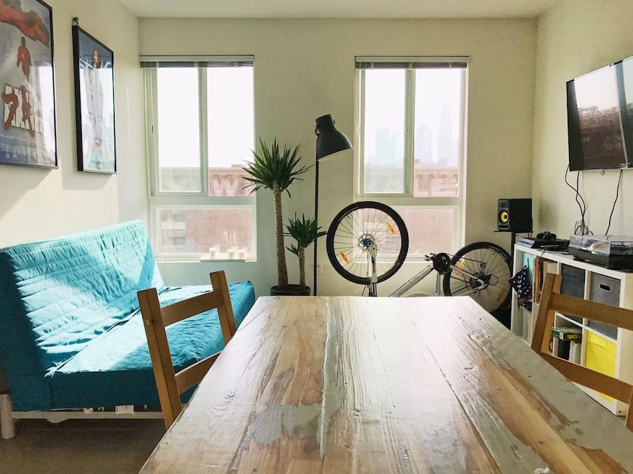 Living room with a double sofa, wooden table, TV, turntable, loudspeakers, PS4