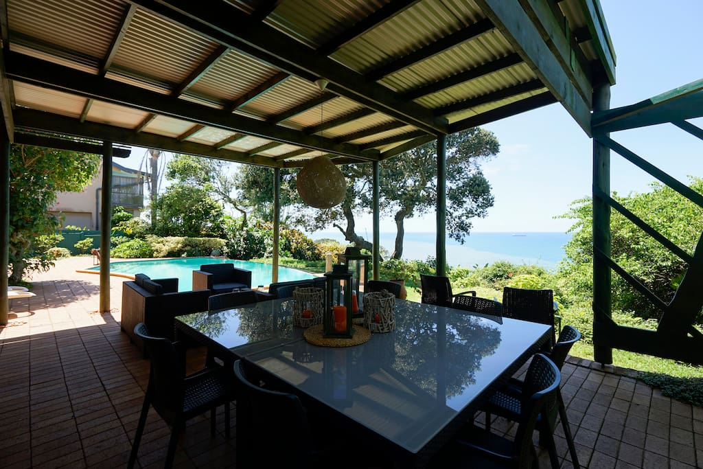 THE LARGE, ROOFED PATIO, POOL AND AWESOME SEA VIEW -- SHOWING THE DINING AREA