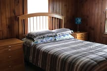 The Bedroom with knotty pine wood and a Queen bed.