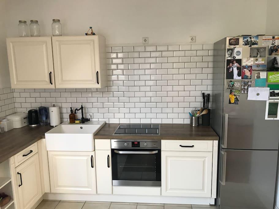 Kochbereich mit Induktions-Kochfeldern, Ofen, Spülmaschine, Kühlschrank, Gefrierschrank und Spülstein
