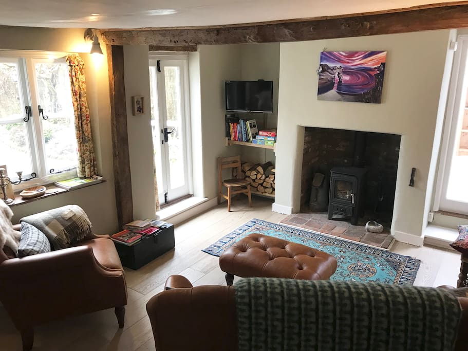 A cosy living room with underfloor heating and a wood burner - views out over the small courtyard garden