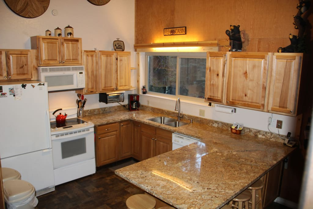 Full stocked kitchen with granite counters and 6 barstools around the peninsula