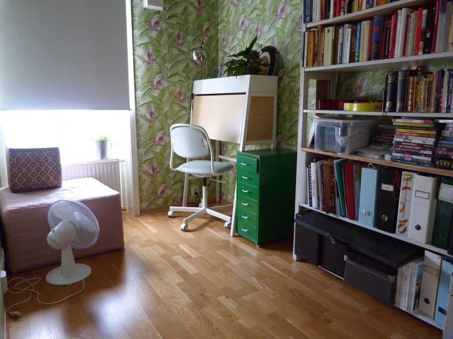 Room with bed folded. Practical desk can be opened and used by guests. Light blocking roll-down curtain.