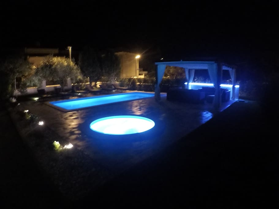 Swimming pool, jacuzzi and pergola at night
