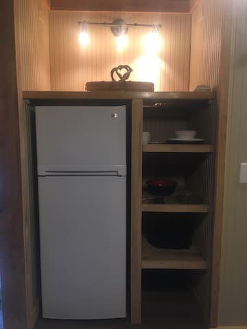 apartment size fridge/freezer and shelving for food, plates etc