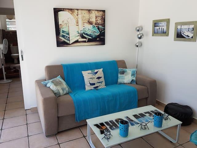 un salon clair équipé d'un canapé lit neuf avec matelas orthopédique