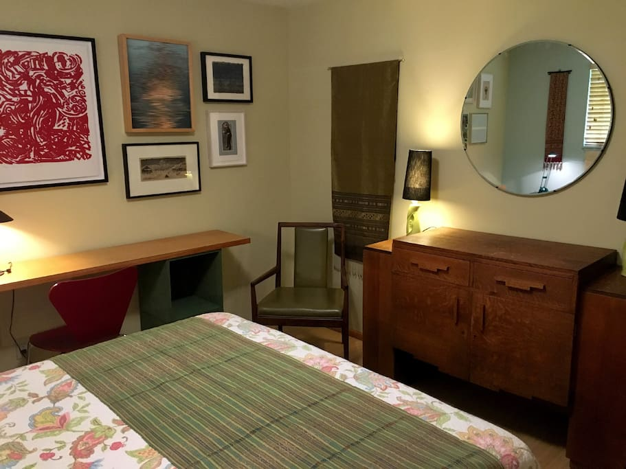 Large bedroom with queen bed, desk, chest of drawers, closet.
