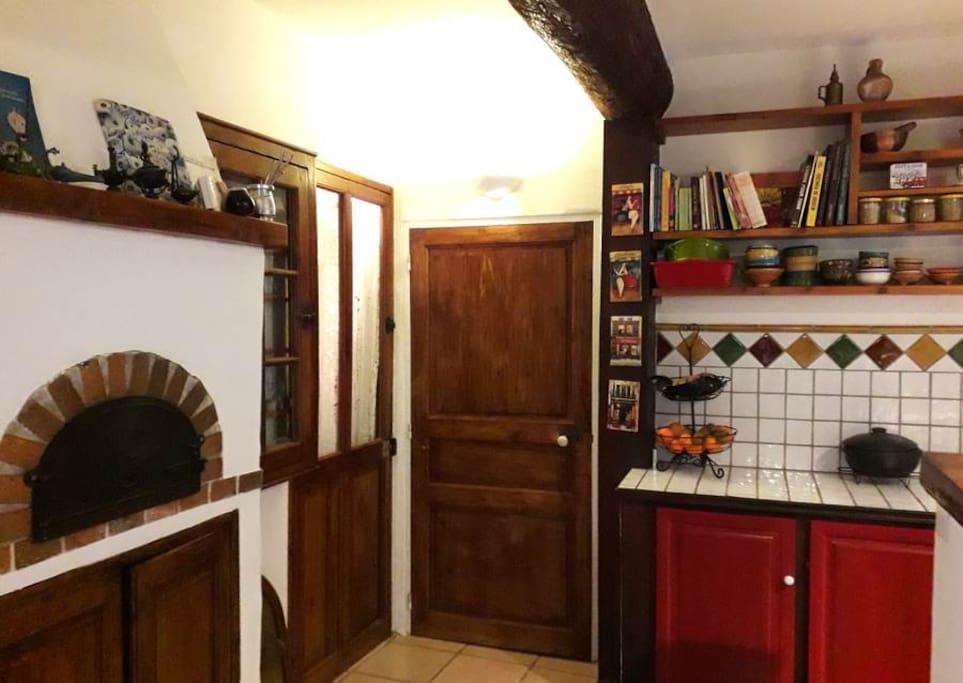 La cuisine (au rez-de-chaussée) avec un four à pizza et une porte qui donne sur le garage.