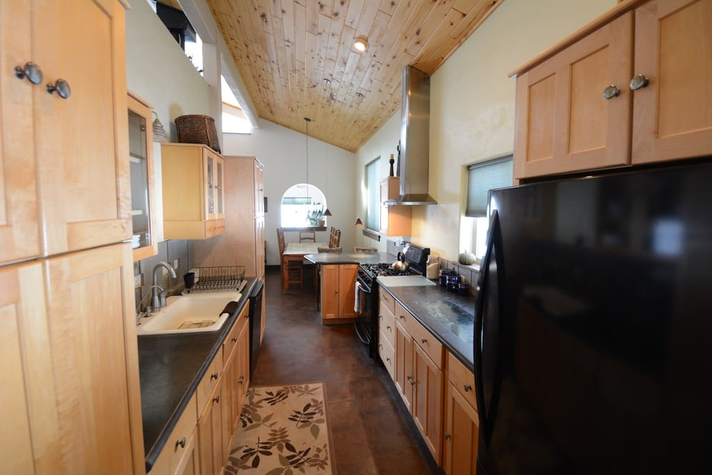 Complete kitchen with convection oven, dishwasher, lots of counter space and large sink.  Marble insert in the concrete counter for you bakers.