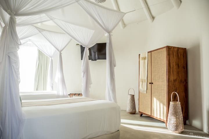 Twin bedroom. The wardrobes are handmade by a local carpenter with sustainable wood and the rooms are serene as you rest to the sound of the ocean waves just outside the door. The beds all have mosquito nets for your comfort. Flat screen TV
