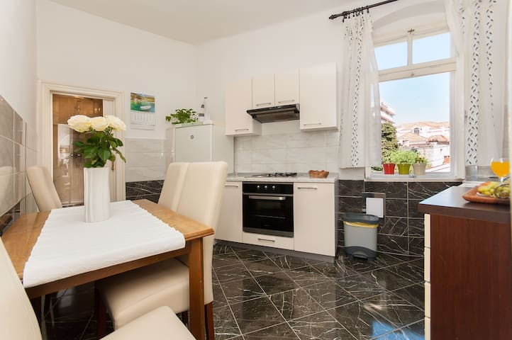 Airy and sunny kitchen including a dishwasher, large fridge and extensive utensils, beautiful sky view.