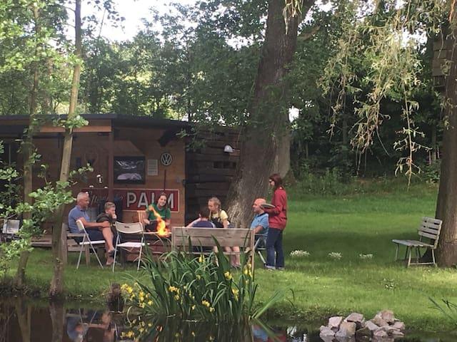 Camper met terrasoverkapping aan vijver glamping