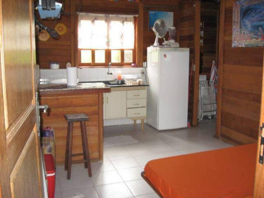 sala com cozinha americana,tv,geladeira,fogão e uma cama de casal