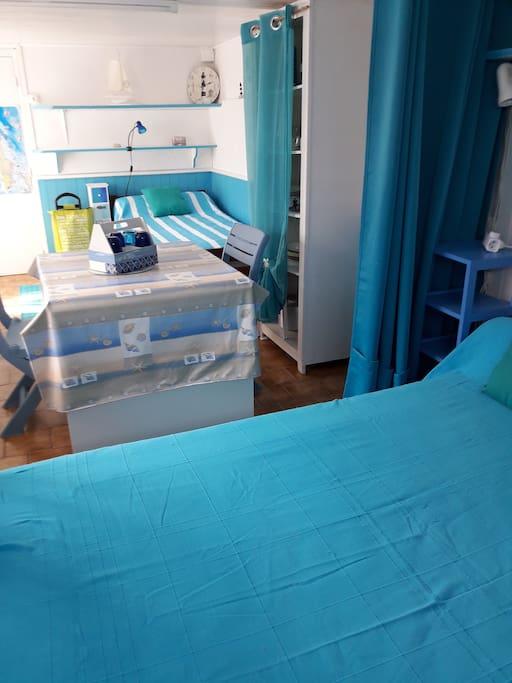 au premier plan lit   2 P avec rideau de séparation, puis table de séjour et au fond lit 1 personne