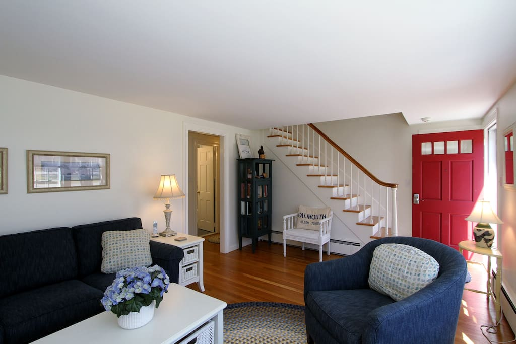 Enter into the main living area, which features original hardwood floors and stair banister.
