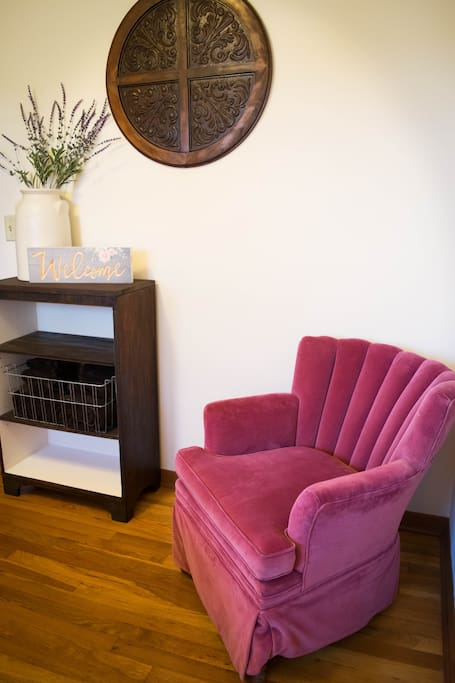This vintage chair makes for a cozy reading corner in the private bedroom.
