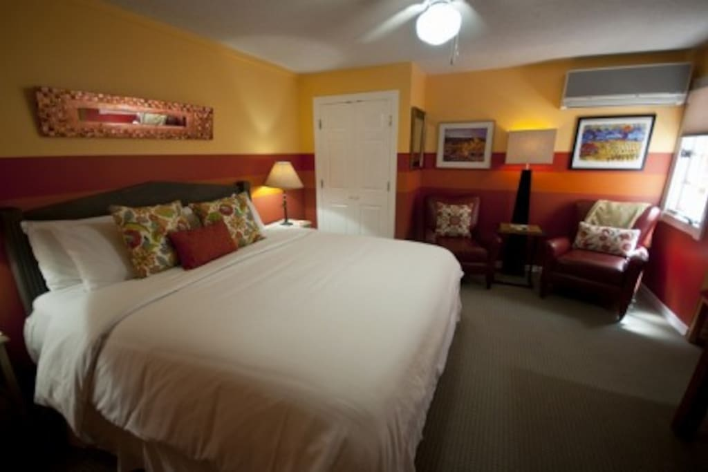Room 8 - This deluxe room features a pillow-top king bed, desk, and large seating for 2.  This is our Wine & Chile Room and it is reflected in the  bright colors and art work.  The historic Plaza is a short 5 minute walk from the Inn and walking distance to Canyon Road, great restaurants, and shopping. Off street parking, WiFi, and full breakfast is included in your rate.