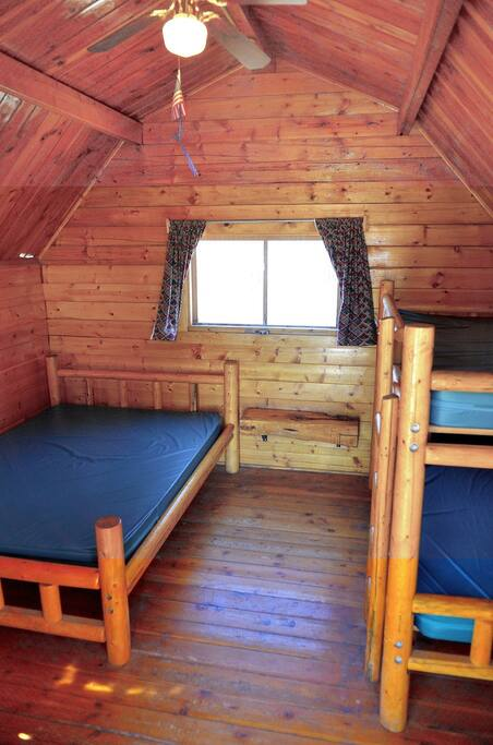 One room cabin with one double bed and a set of bunk beds.