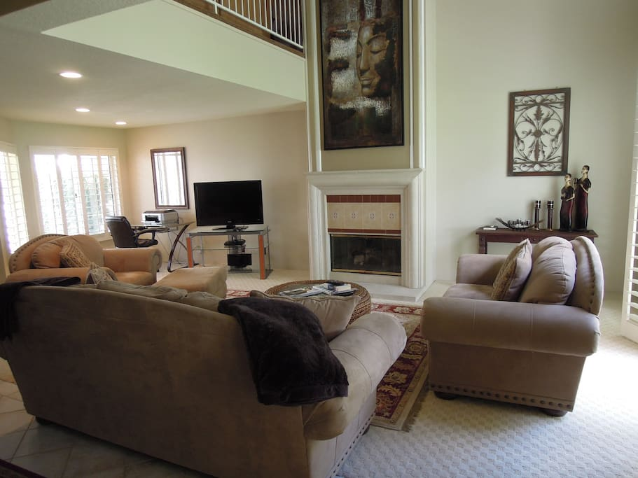 Spacious living room with TV, gas fireplace and work desk.