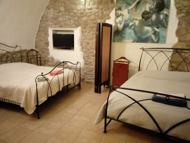 Area notte dell'open space utilizzabile da 2 a 4-5 persone con l'aggiunta di un letto. Da notare l'avvolgente volto a botte e l'originale architettura della parete con sassi di fiume a vista.