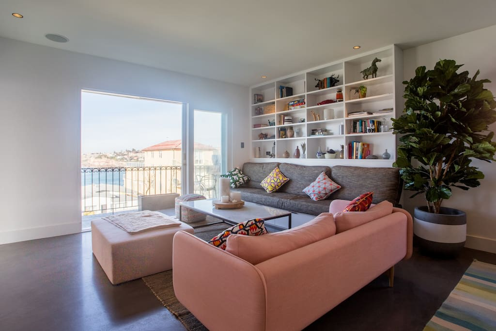 Living and entertaining area with panoramic ocean views, extending to terrace with BBQ