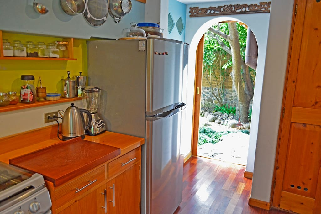 Fully equipped kitchen with full fridge, door private garden
