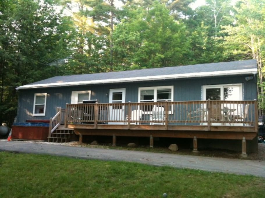 Front of house with large deck, stainless steel grill, and 6-person hot tub overlooking Newfound Lake.