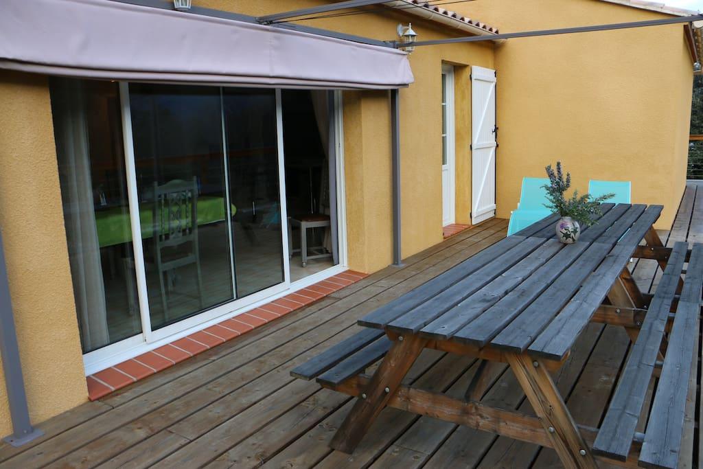 terrasse ensoleillée longues chaises et barbecue
