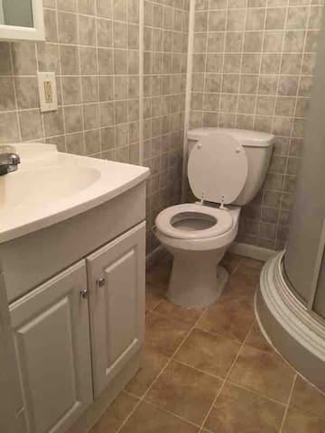 Bathroom with toilet, sink &  shower stall.