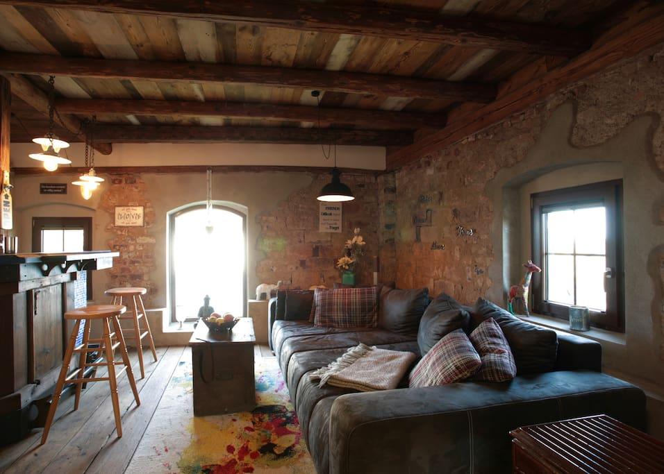 Wohnbereich mit großer Couch und Bar