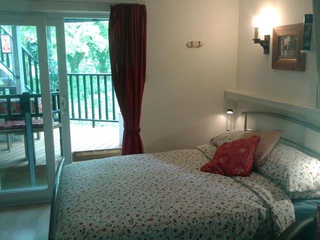 the double bed is next to lounge  and has direct access to the balcony and hot tub   / Mae gwely dwbwl `fforddus wedi leoli mewn gosodiad stiwdio ond yn gyfleus ir twb twym .