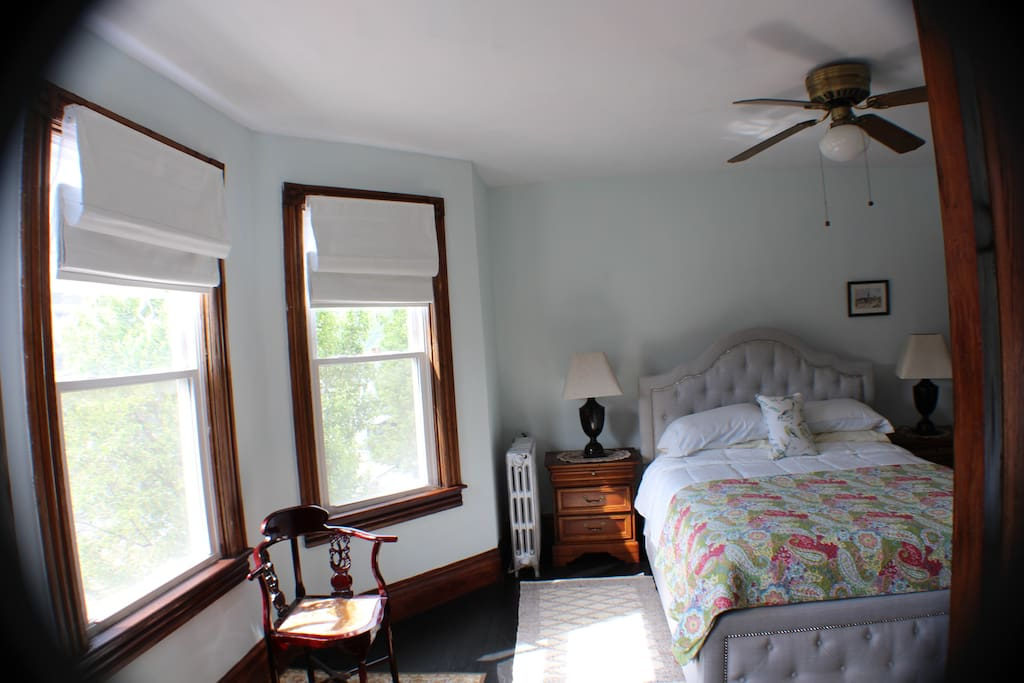 Queen bed with new (3) window treatments facing the front of townhouse