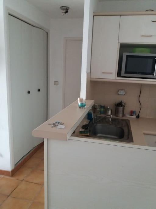 La cuisine équipée de four, micro onde, frigo, plaques et vaisselle