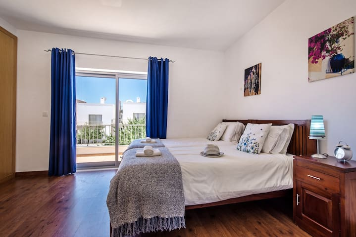 1st floor twin. bedroom with access to a balcony and the roof terrace
