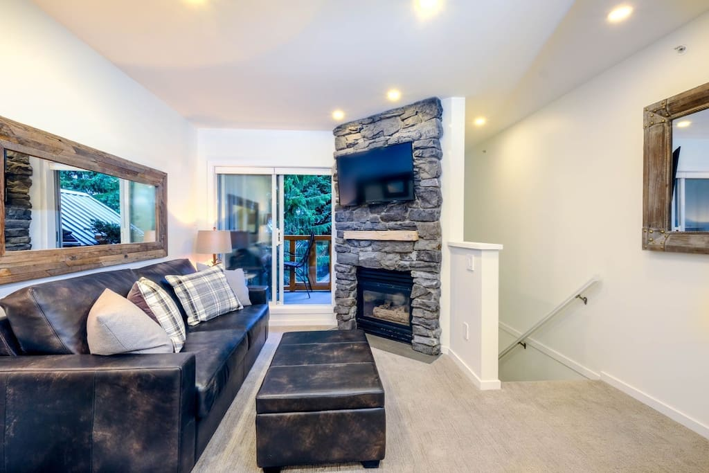 A comfortable living room with rock surrounded gas fireplace. Custom leather sofa bed adds a practical feature for your stay.