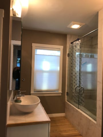 Contemporary bathroom with tub and shower behind glass doors.