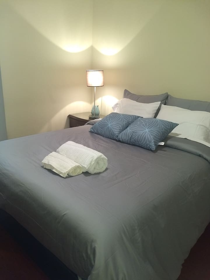 Habitación privada con cama doble confortable, closet, perchero, escritorio, bien iluminada.