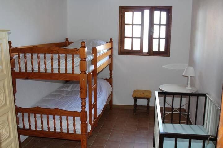 Chambre avec lits superposés + lit bébé.