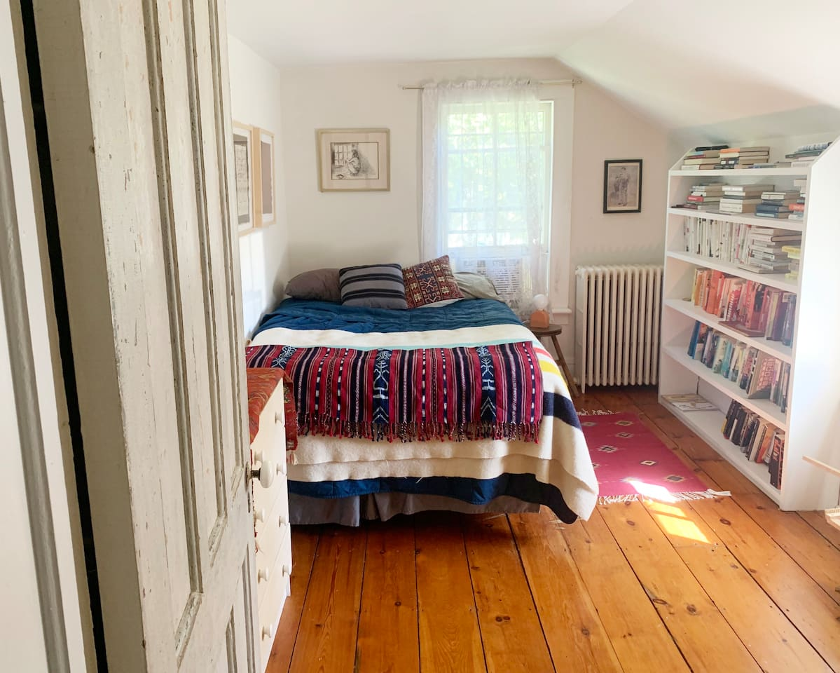 The guest room with full size bed, two windows, built in book shelves, a small chest of drawers, and closet.