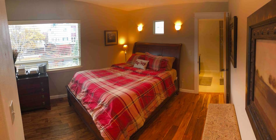 Warm and inviting guest room with a queen bed, dresser, and attached bathroom.