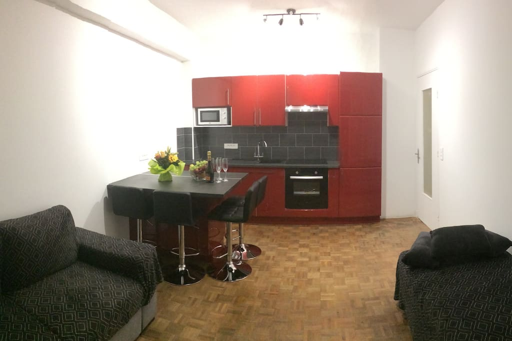 Main room with americain kitchen has a comfortable sofe, TV and  Air Conditionning