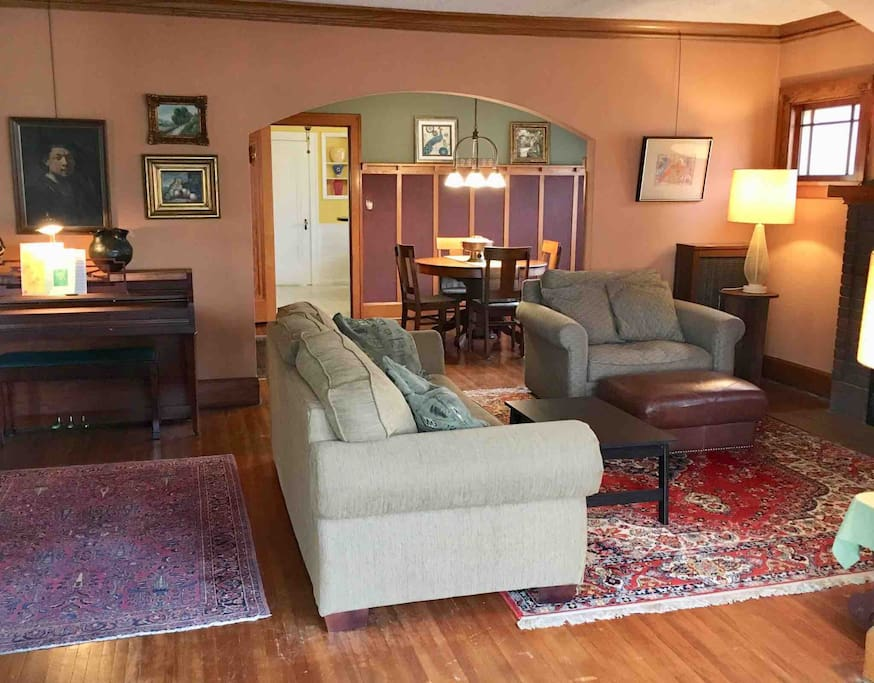 Inviting Living Room with Comfortable Seating, and Piano.  The Living Room naturally blends into the Arts and Crafts Dining Room with Buffet.