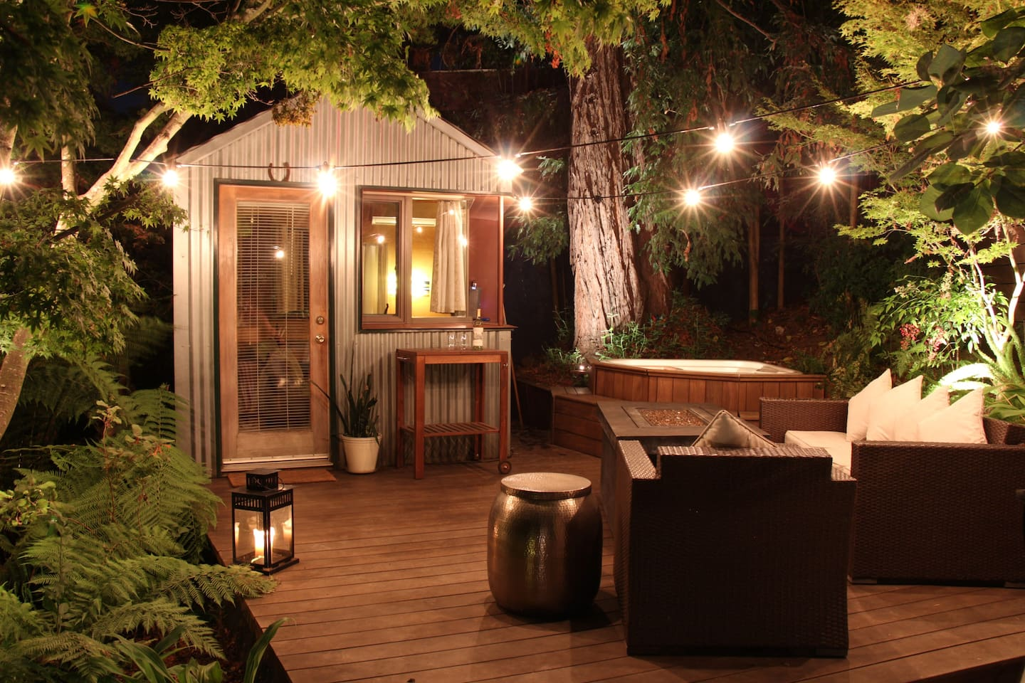 "The ""Redwood Room"" lit up at night with ambient landscape lighting and Edison string lights make for a magical evening."