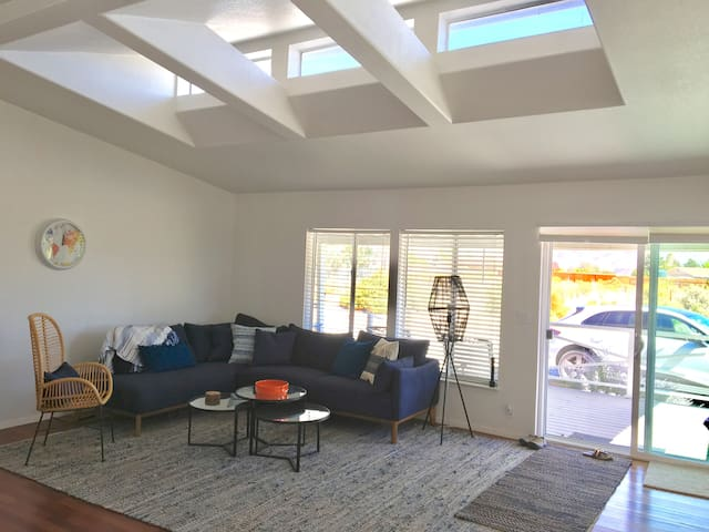 Natural light spills into the comfortable living room from the skylights & high vaulted ceilings...