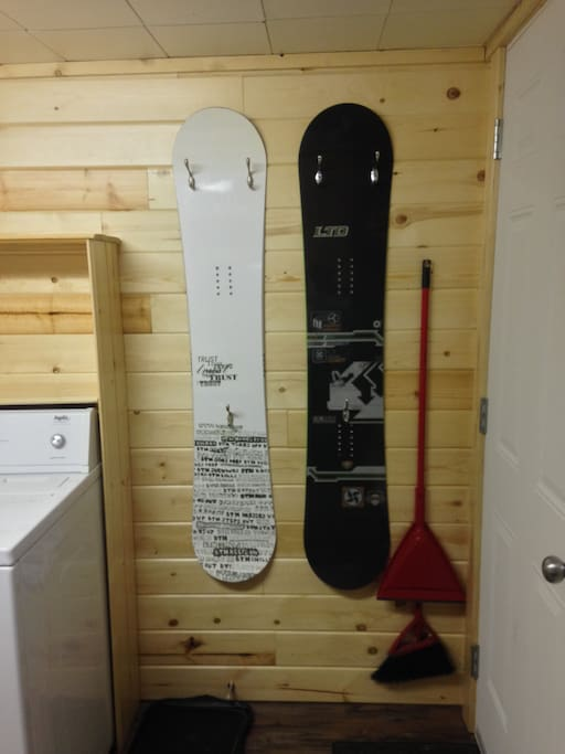 Snowboards with hooks for coats and stuff at door.