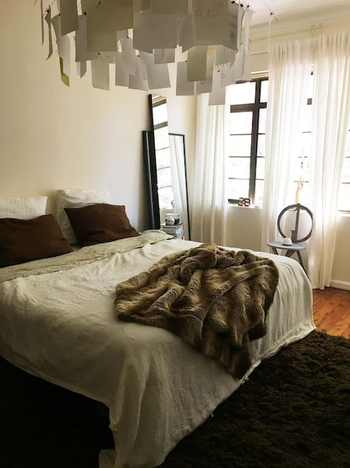 Luxuriously huge bedroom with chic linen sheets and king size bed, looking onto treelined street