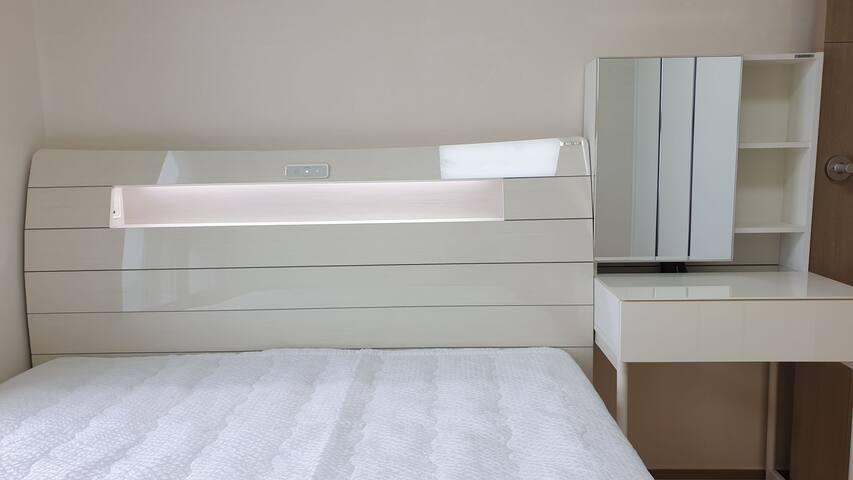 에몬스의 고급 침대와 화장대에 드라이기와 헤어아이롱이 구비되어 있습니다